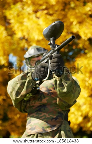 paintball player in prootective uniform and mask aiming and shoting with marker outdoors