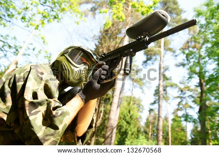 paintball player in protective uniform and mask aiming and shooting with paint marker gun outdoors - stock photo
