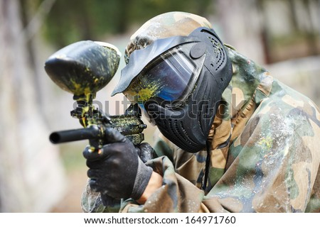 paintball player in protective uniform and mask aiming gun before shooting in summer - stock photo