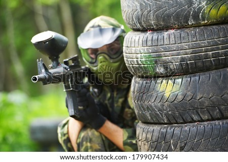 paintball player in protective uniform and mask aiming marker gun in summer - stock photo