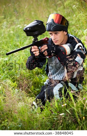 paintball shooter aiming the gun - stock photo