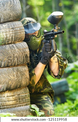 paintball sport player in protective uniform and mask aiming and shooting with gun outdoors