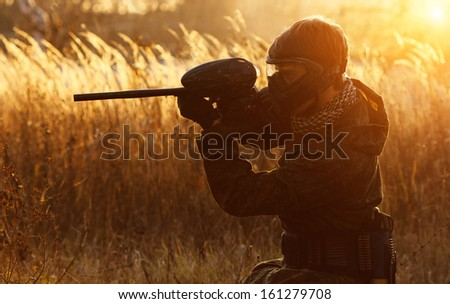 Paintball sport player in protective uniform and mask aiming gun before shooting at sunset - stock photo