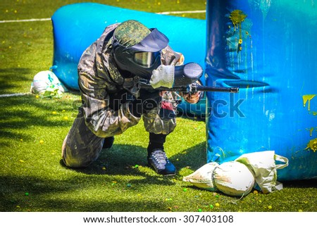 Paintball sport player in protective uniform and mask playing with gun outdoors - stock photo