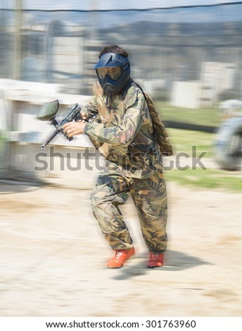 Paintball sport player wearing protective mask aiming gun and shoted down  - stock photo