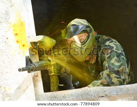 paintball sport player wearing protective mask aiming gun under attack with paint splash - stock photo