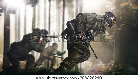 Paintball team in action forest location - stock photo