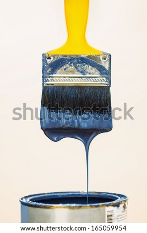Paintbrush after dipping it into bucket. - stock photo