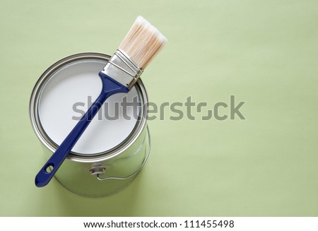Paintbrush and a newly opened can of white paint on green background. - stock photo