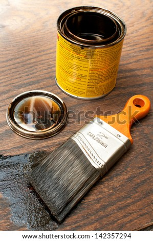 Paintbrush and open tin with dark paint - stock photo
