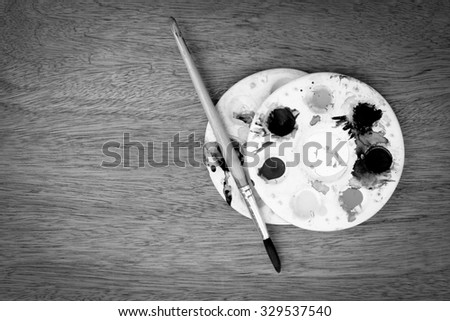 paintbrush and watercolor pallete on wooden background ,black and white tone - stock photo