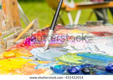 Paintbrush mixing colors on the multicolored palette of blended oil paints outdoors - stock photo