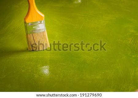 Paintbrush on green painted background. - stock photo