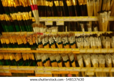 Paintbrush on shelf in stationery store, abstract blurry background