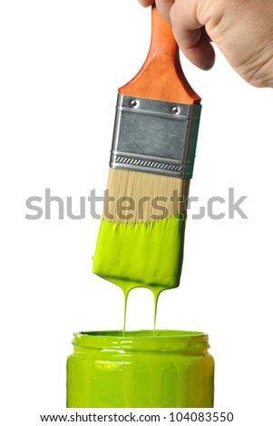 Paintbrush with green paint dripping into container isolated over white background - stock photo