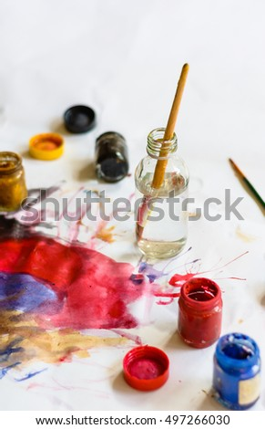 paintbrushes and color water bottle for painting with paper
