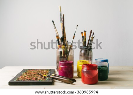Paintbrushes and colors on a table - stock photo