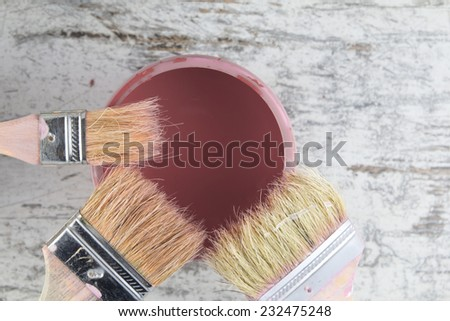 Paintbrushes and paint can in a wood background, vintage - stock photo