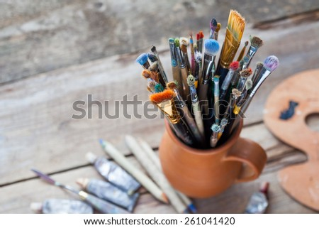 Paintbrushes in a jug from potters clay, palette and paint tubes on desk. - stock photo