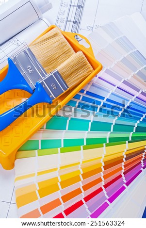 paintbrushes in paint can on color paleteed and rolled blueprints  - stock photo