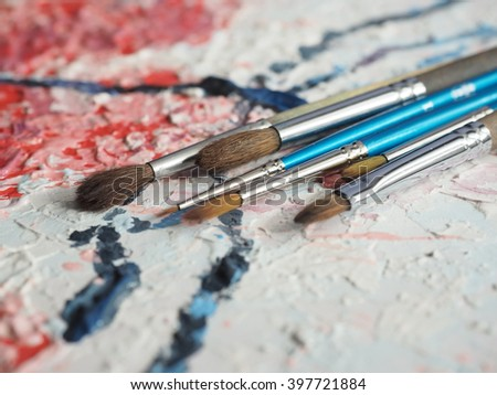Paintbrushes on oil painting canvas. Shallow depth of field. - stock photo