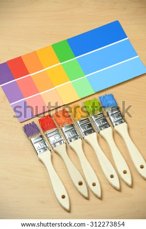 PAintbrushes with different colors with paint samples on wooden table
