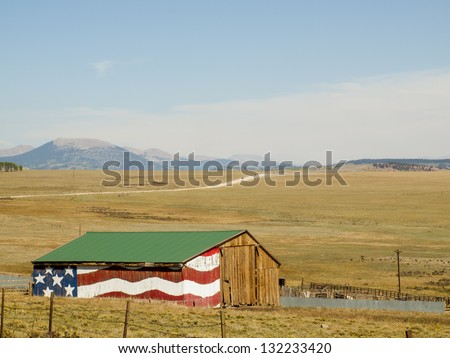Painted big American Flag on exterior of old barn in Colorado. - stock photo