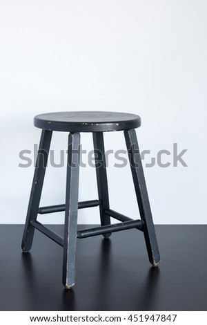 Painted black shabby stool on wooden surface.