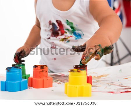 painted child's hand and colors isolated on white background - stock photo