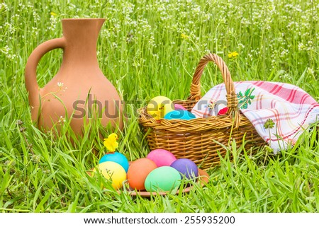Painted Easter eggs and toy chicks on a background clay pitcher, a wicker basket under the checkered napkin and green spring grass - stock photo
