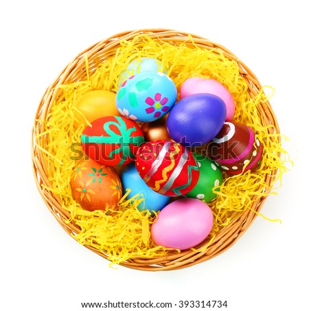 Painted Easter eggs in wicker nest isolated on white