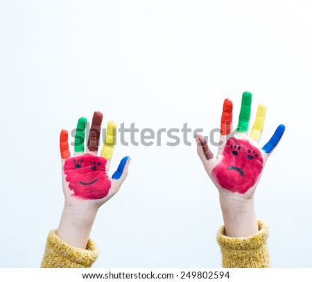 Painted hand faces, smile and sad - stock photo