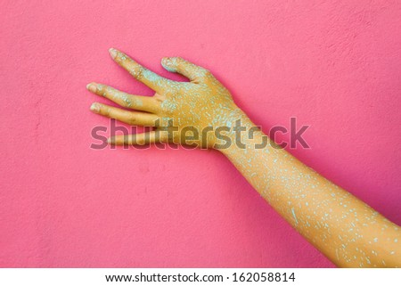 Painted hand on the pink wall. - stock photo