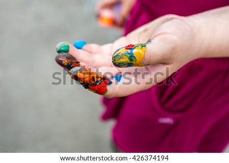 Painted  hand, outdoor shot, selective focus on fingers - stock photo