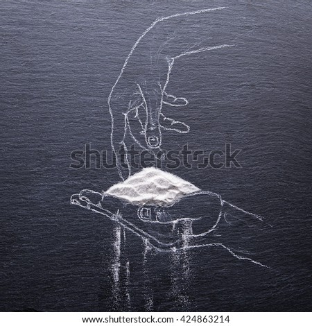 Painted hand tries to keep the sand that pours through his fingers on slate board - stock photo