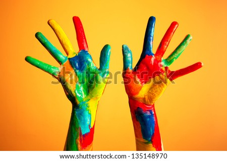Painted hands, colorful fun. Creative, funny and artistic means happy! Orange background wall - stock photo