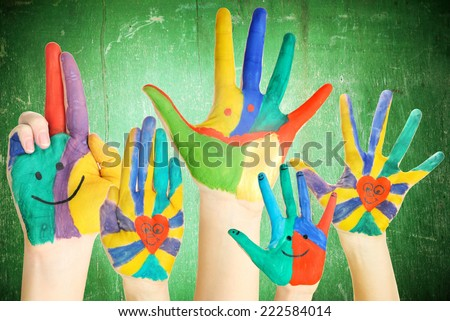 Painted hands on wooden background - stock photo