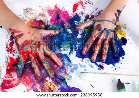 Painted hands smudging colors on messy paper - stock photo