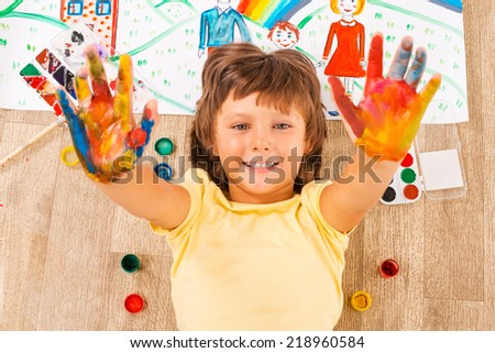 Painted hands. Top view of happy little boy showing his palms coated in colorful paint while lying on the floor - stock photo