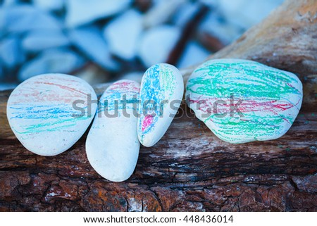 painted in different colors of a child's hand sea pebbles lying on a tree. - stock photo