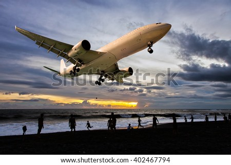 Painted in sunset colors passenger plane. Aircraft is flying over the beach and people, which playing football. - stock photo
