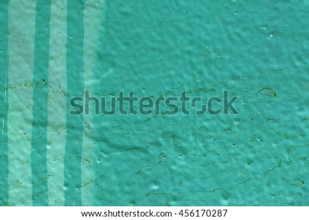 Painted lines on dirty green wall surface. Abstract background.