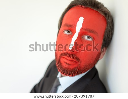 Painted man with red face and white line on nose