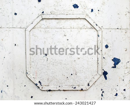 Painted metal surface with metal frame of old white paint craquelure