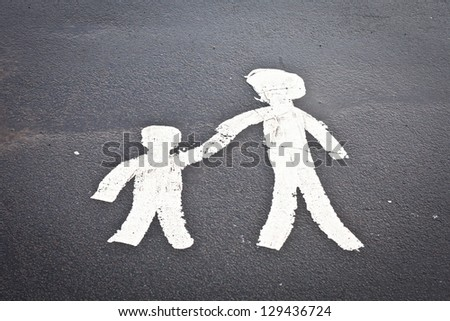 Painted parent and child sign on a tarmac surface