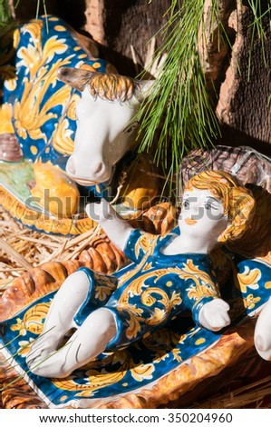 Painted pottery statue portraying baby Jesus in the ceramic nativity scene of an artisan in Caltagirone - stock photo