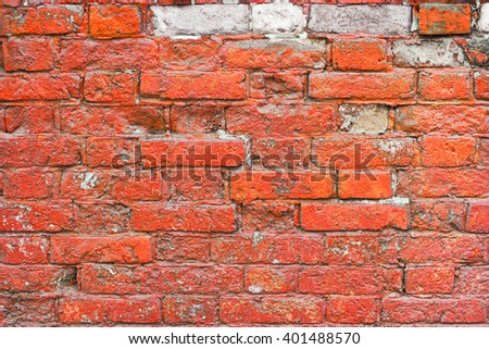 Painted red brick wall with weathered plaster background texture. Old painted brick wall texture. Background of old vintage dirty brick wall with peeling plaster. - stock photo