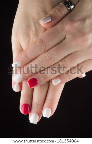 Painted red white nails and hands isolated on black background