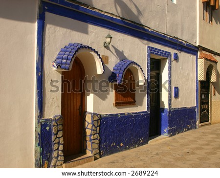 Painted store fronts in the medina district of Asilah Morocco - stock photo