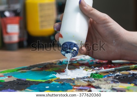 Painter adding colors on palette